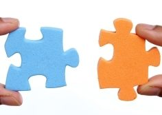 Blue puzzle piece plugging or fitting into orange puzzle piece.